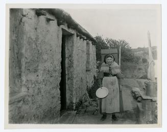 Old lady outside a cottage in Jurby