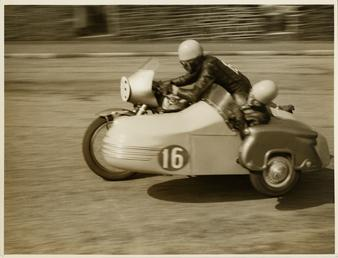 Eric Oliver driving sidecar outfit (number 16) and…
