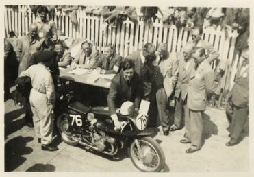 Geoff Duke pushing Gilera number 76 away from…