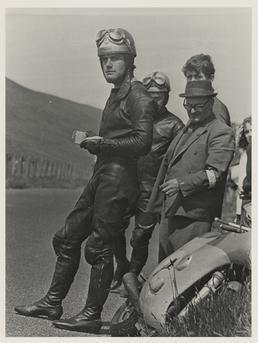Giacomo Agostini with bike at side of road,…