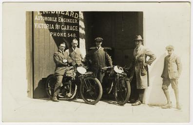 Group of riders and mechanics outside the garage…