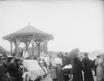 Spectators watching a pierrot show at bandstand on…