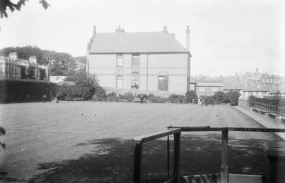 Bowling green with large house behind, possibly Derby…