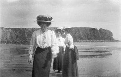 Three women in Edwardian dress on the beach,…
