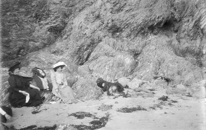Two woman sitting on rocks below a cliff,…