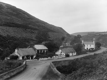 Thatched cottage and houses, road at Ballig