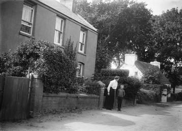 Two-storey house with woman and boy.in front of…