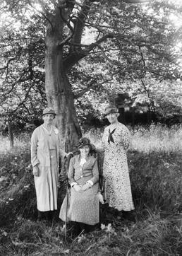 Three women in formal pose in front of…