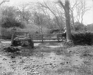 Fairy bridge over stream with person seated right