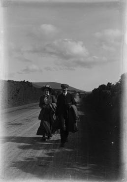 Man and woman walking down road, Isle of…