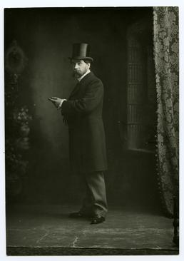 Mr Archibold Knox, standing in top hat and…