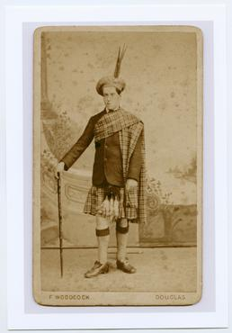 Studio portrait of Archibald Knox in Scottish Dress