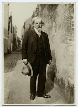 Archibald Knox standing in narrow lane behind 70…