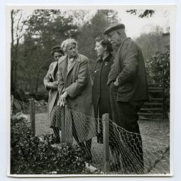 T.W. Stowell, standing outside with three ladies