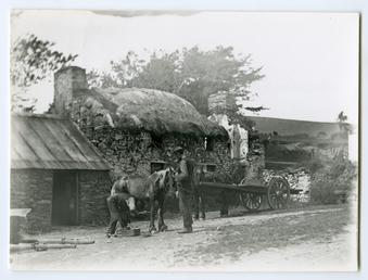 Thatched smithy with horse and cart outside